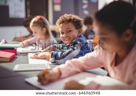 Portrait of smiling schoolboy doing his homework in classroom at school