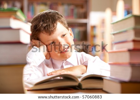 Portrait of smiling schoolboy sitting at the table with books on it