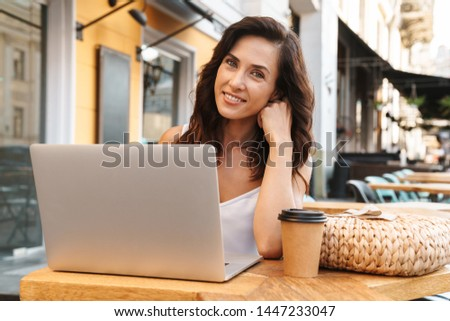 Portrait of smiling seductive woman with straw bag drinking coffee from paper cup and using laptop while sitting in cozy cafe outdoors #1447233047