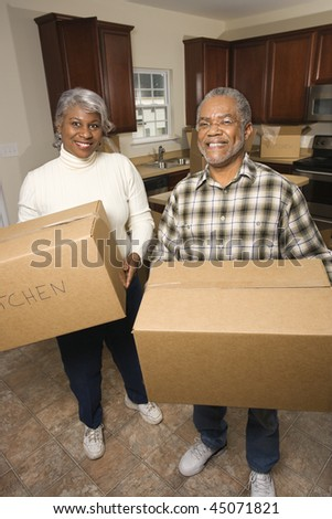 Portrait of smiling senior african american man and woman with moving boxes in a new home.   Vertical shot.