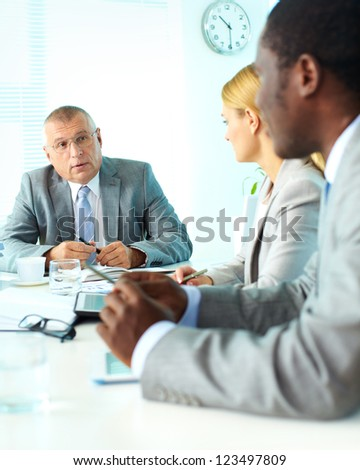 Portrait of smiling senior boss looking at his employees at meeting