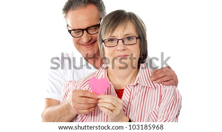 Portrait of smiling senior couple looking at camera with focus on paper heart