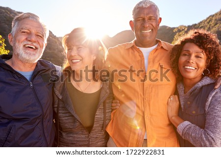 Portrait Of Smiling Senior Friends Walking In Countryside Together