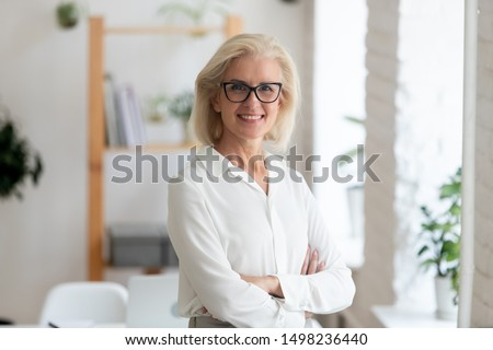 Portrait of smiling senior grey-haired beautiful businesswoman stand with arms crossed posing for picture at workplace, happy confident aged woman worker or company ceo in glasses look at camera
