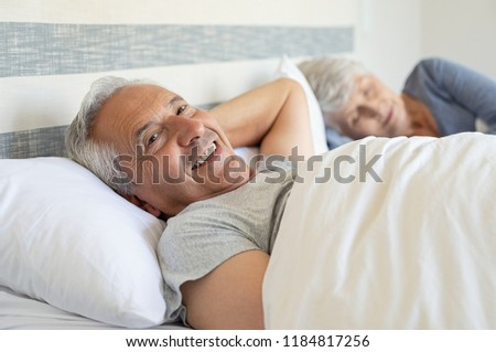 Portrait of smiling senior man lying in bed while his wife sleeping in background. Old couple resting in bedroom during afternoon time. Happy matured man looking at camera under the blanket.
