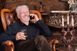 Portrait of smiling senior man talking on phone