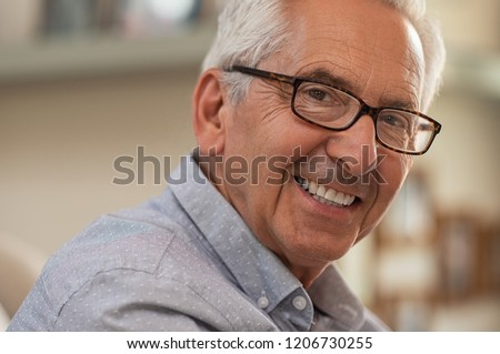 Portrait of smiling senior man with eyeglasses looking at camera. Successful mature man wearing spectacles at home. Closeup face of handsome elder with glasses and toothy smile. #1206730255