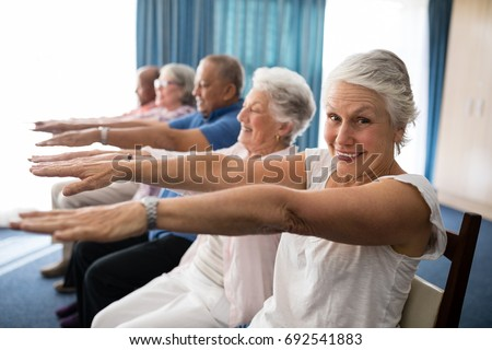 Portrait of smiling senior woman exercising with friends at retirement home