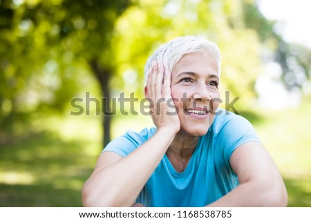 Portrait of smiling senior woman relaxing after exercising while sitting on grass
