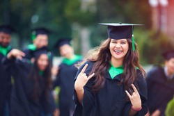 portrait of smiling successful indian student in graduation gown with rock n roll hand gesture