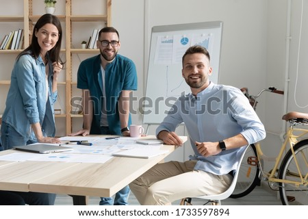 Portrait of smiling team with documents in coworking boardroom looking at camera. Happy diverse corporate staff in negotiation, bank workers photo shoot, HR agency recruitments.