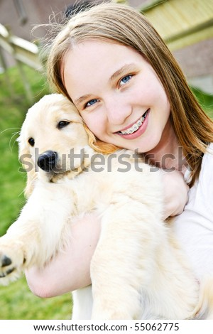 Portrait of smiling teenage girl holding golden retriever puppy