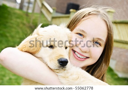 Portrait of smiling teenage girl holding golden retriever puppy - stock photo