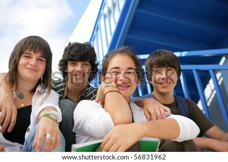 Portrait of smiling teenagers sitting on the steps of stairs