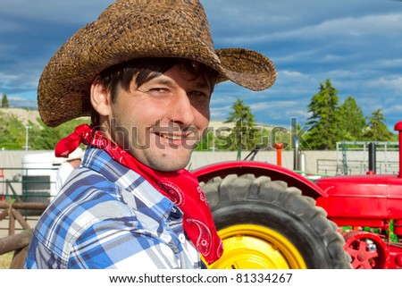 Portrait of smiling tractor driver wearing cowboy hat, silk scarf, and checked shirt. Photo is taken during Calgary Stampede 2011
