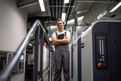 Portrait of smiling typographer standing by printing machine in print house.