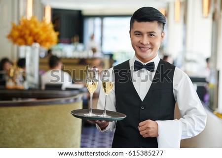 Portrait of smiling Vietnamese waiter serving drinks in restaurant #615385277