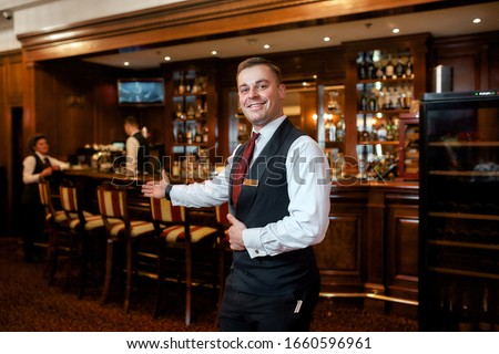 Portrait of smiling waiter welcoming guests in hotel restaurant. Horizontal shot