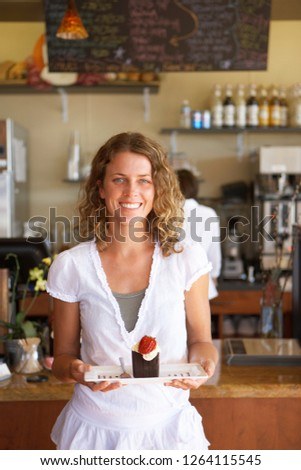 Portrait of smiling waitress working in cafe carrying chocolate dessert on plate to serve #1264115545