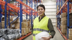 Portrait of smiling warehouse worker asian korean woman wearing safety vest and holding hard hat and looking in camera while standing in stockroom