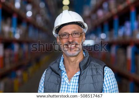 Portrait of smiling warehouse worker wearing hard hat in warehouse