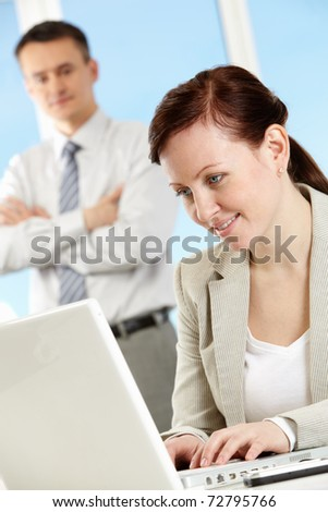 Portrait of smiling woman at workplace touching keypad of laptop