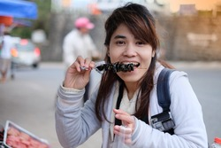 Portrait of smiling woman eating, young asian is happy to eat, a female tourist enjoy eating traditional street food in Dalat, Vietnam