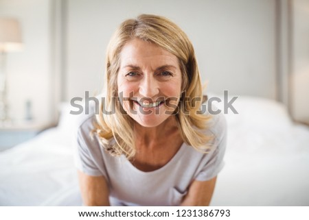 Portrait of smiling woman in bedroom at home