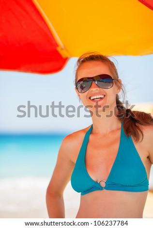 Portrait of smiling woman on beach under umbrella