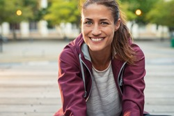 Portrait of smiling woman sitting on floor of city street after running. Healthy mature runner resting after workout exercise and looking at camera. Active sporty woman enjoying outdoors in autumn.