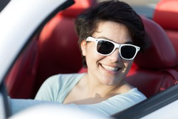 Portrait of smiling woman wearing sunglasses in a convertible sports car with red leather interior.