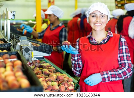 Portrait of smiling woman with peaches in her hands next to the fruit sorting line Foto stock ©
