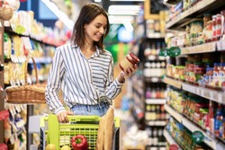 Portrait Of Smiling Woman With Shopping Cart In Supermarket Buying Groceries Food Walking Along The Aisle And Shelves In Grocery Store, Holding Glass Jar Of Sauce, Choosing Healthy Products In Mall