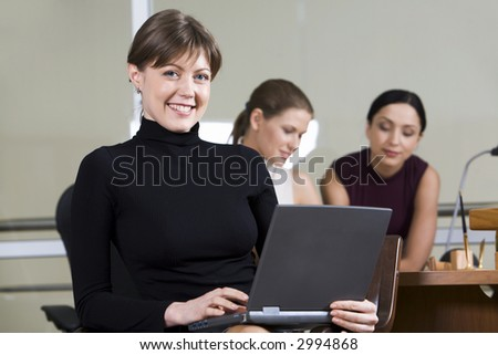 Portrait of smiling woman with the laptop on her knees sitting in the café and two girls on the background