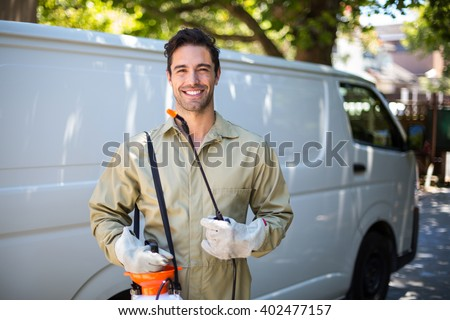 Portrait of smiling worker with pesticide sprayer while standing by van Foto d'archivio ©