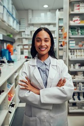 Portrait of smiling young african american woman pharmacist wearing labcoat standing in chemist