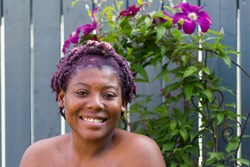 Portrait of smiling young African-American woman with braided and magenta died hair with blue fence and creeping flowers background