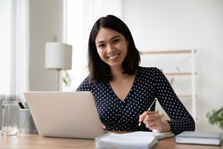 Portrait of smiling young asian female student study online or take web course training on computer. Happy Vietnamese woman make notes work on laptop from home office. Distant education concept.