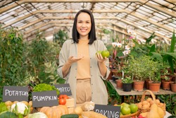 Portrait of smiling young Asian gardener recommending to eat apples while selling organic product at farmers market