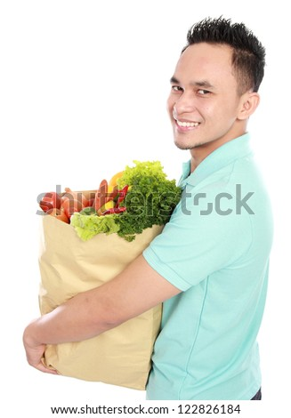 Portrait of smiling young asian Man with paper bag full of fruits and vegetables isolated on white background