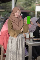 Portrait of smiling young Asian teenager girl showing blank green phone screen while friends sitting in background on cafe or eatery