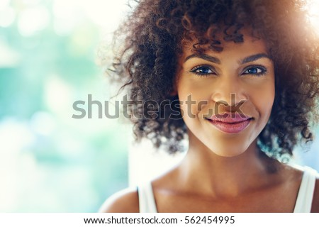Portrait of smiling young black woman with sunlight flare and copy space #562454995