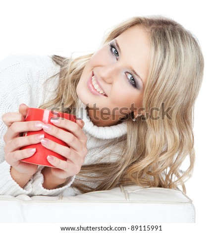 Portrait of smiling young blonde woman holding cup of coffee or tea over white