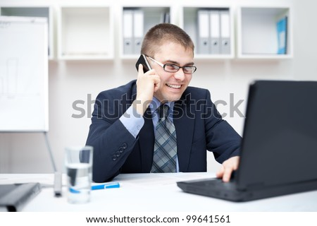 Portrait of smiling young business man talking on cell phone and working on a laptop at office