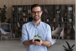 Portrait of smiling young businessman hold soil and small plant launch startup project or activity. Happy millennial male employee or CEO with seedling sprout in hands. Growth, development concept.