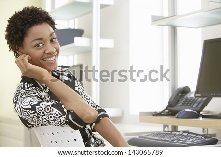 Portrait of smiling young businesswoman sitting at computer desk in office