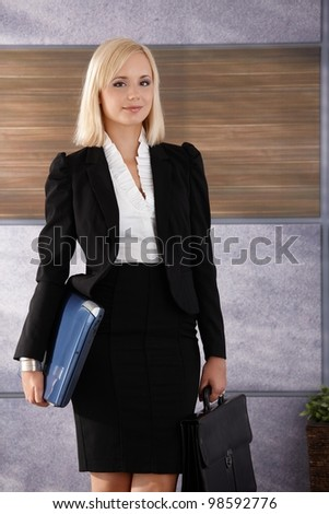 Portrait of smiling young businesswoman standing in office with laptop computer and briefcase handheld.
