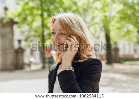 Portrait of smiling young businesswoman talking with cell phone, adult female manager using mobile phone for a call, happy successful manager having a conversation talk holding model gadget  #1082584115