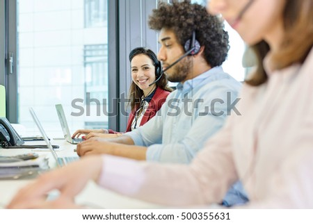 Portrait of smiling young businesswoman using headset and laptop with colleagues in foreground at office - Shutterstock ID 500355631