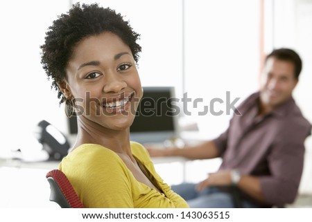 Portrait of smiling young businesswoman with male colleague in background